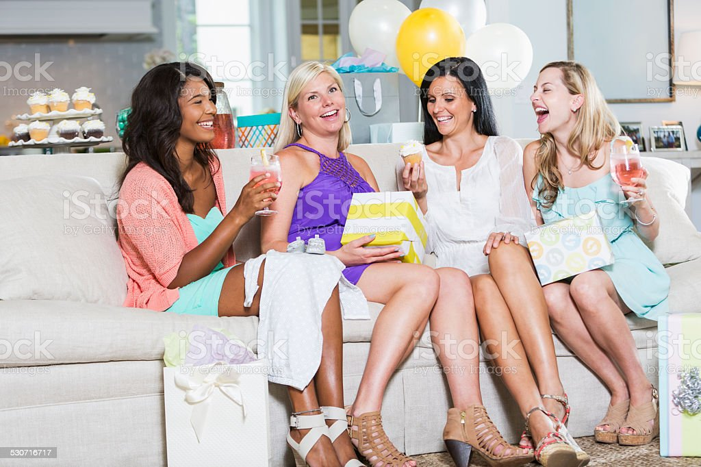 Four multiracial friends at a baby shower, sitting on a couch opening...