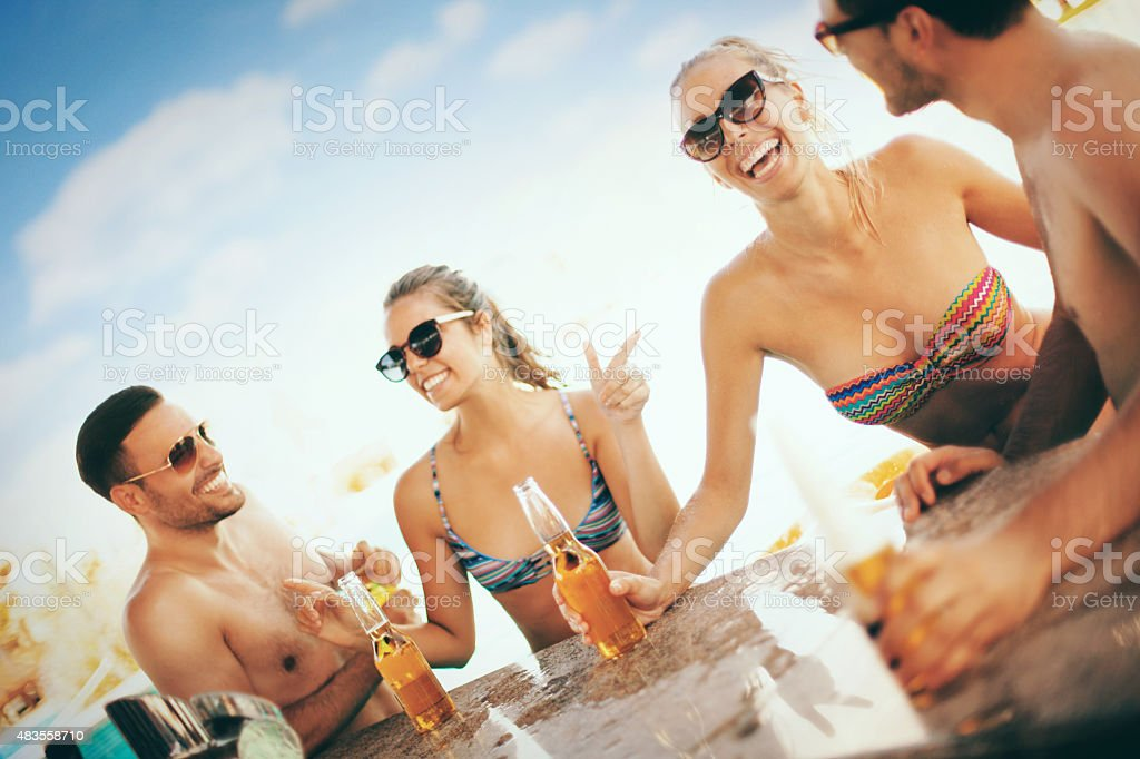 Friends having fun at beach bar. stock photo