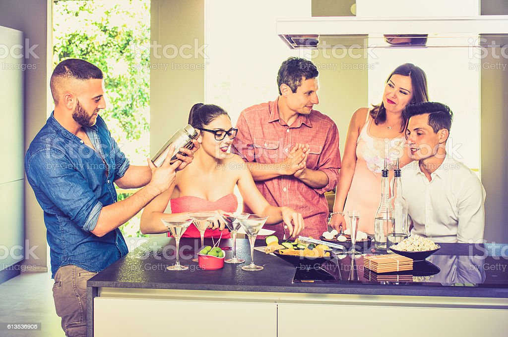 Friends having fun at house party with pre dinner cocktails stock photo
