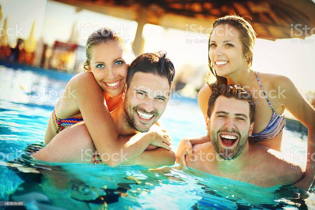 Friends having fun at swimming pool. stock photo