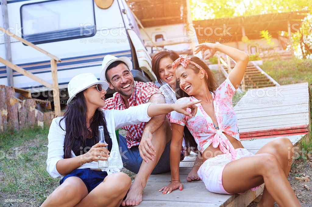 Friends having fun behind the caravan stock photo