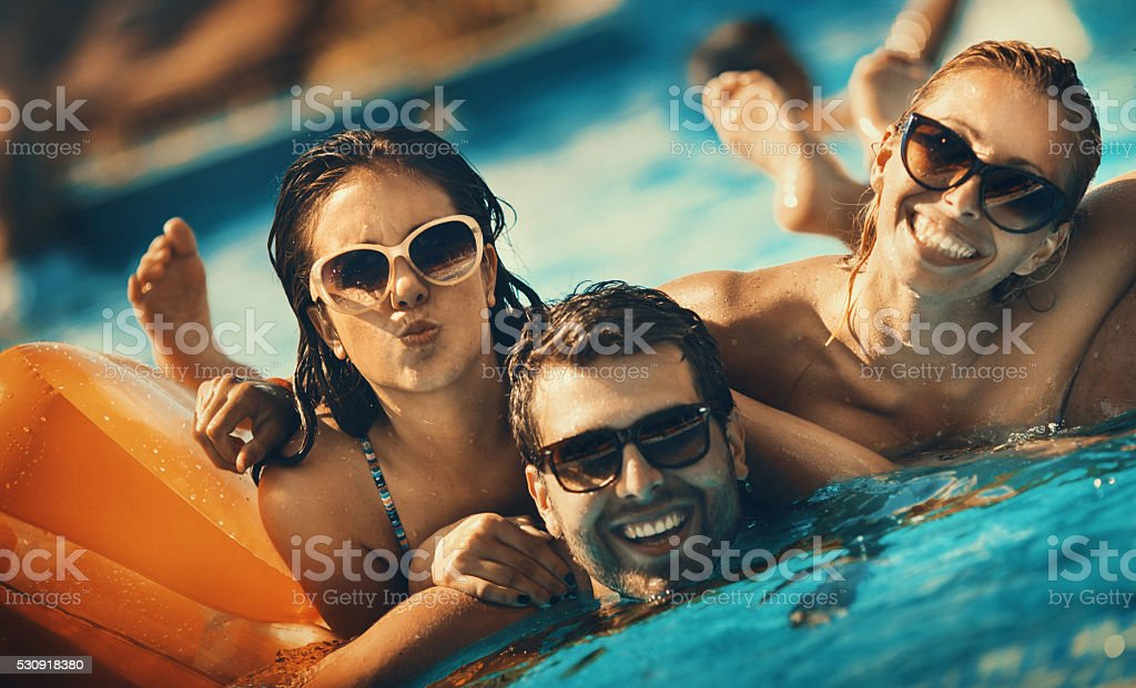 Friends having fun in a swimming pool. stock photo
