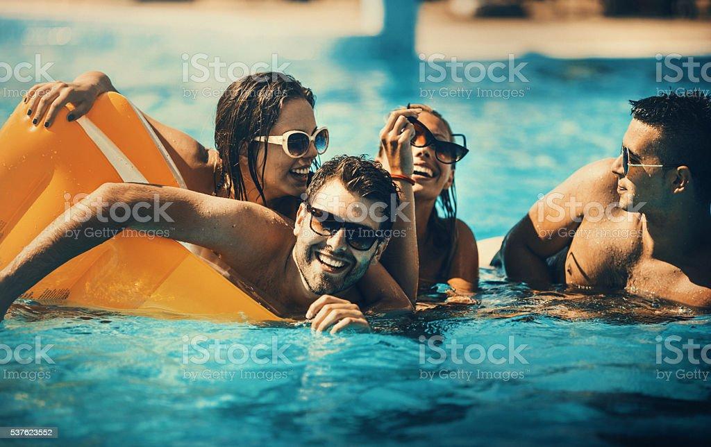 Friends having fun in a swimming pool. stock photo