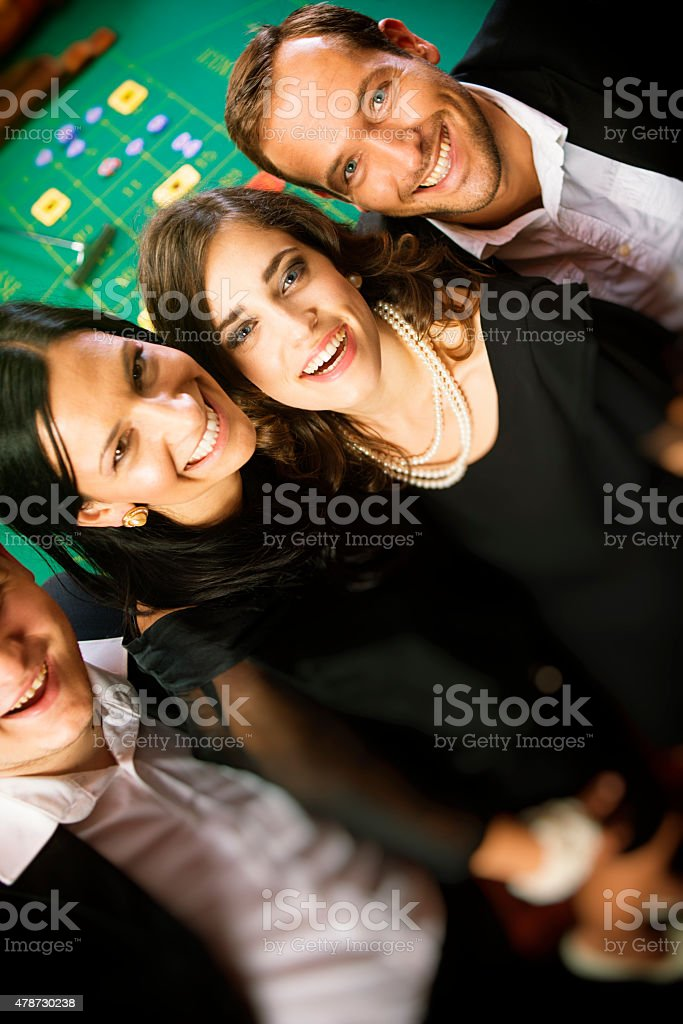 Friends Having Fun in Casino at Roulette Table stock photo