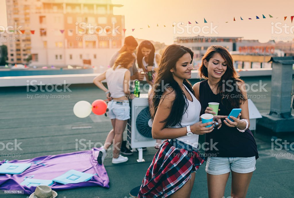 Friends having fun on a birthday party at the rooftop stock photo