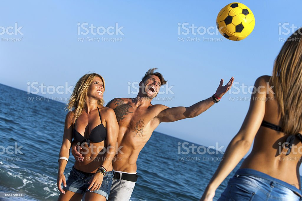Friends having fun on beach with ball. royalty-free stock photo