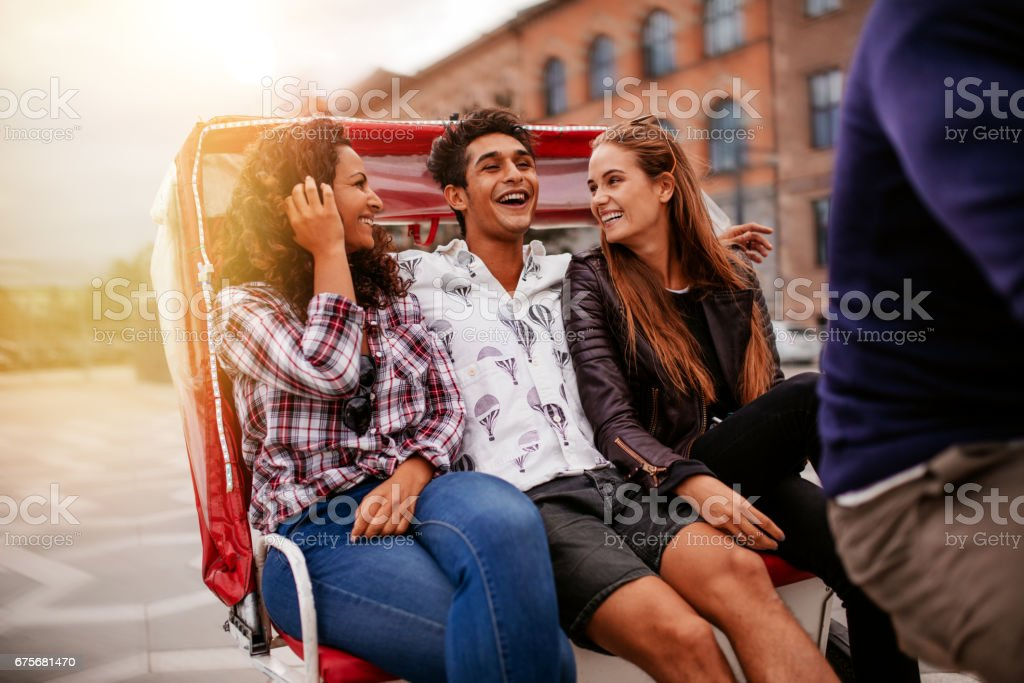 Friends having fun on tricycle ride stock photo