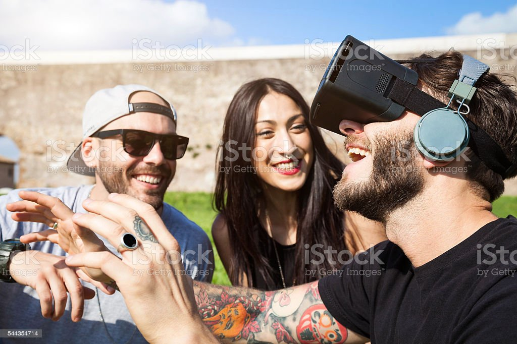Friends having fun outdoors at the park with VR Headset stock photo