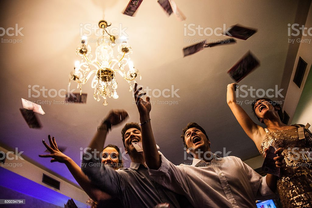 Friends having fun with money in the casino stock photo