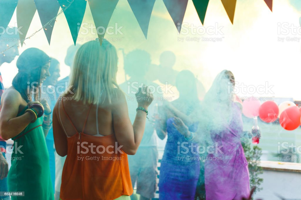 Friends having fun with smoke bomb on a rooftop party stock photo