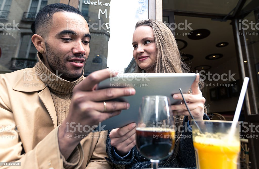 Friends having fun with their digital tablet at a cafe stock photo
