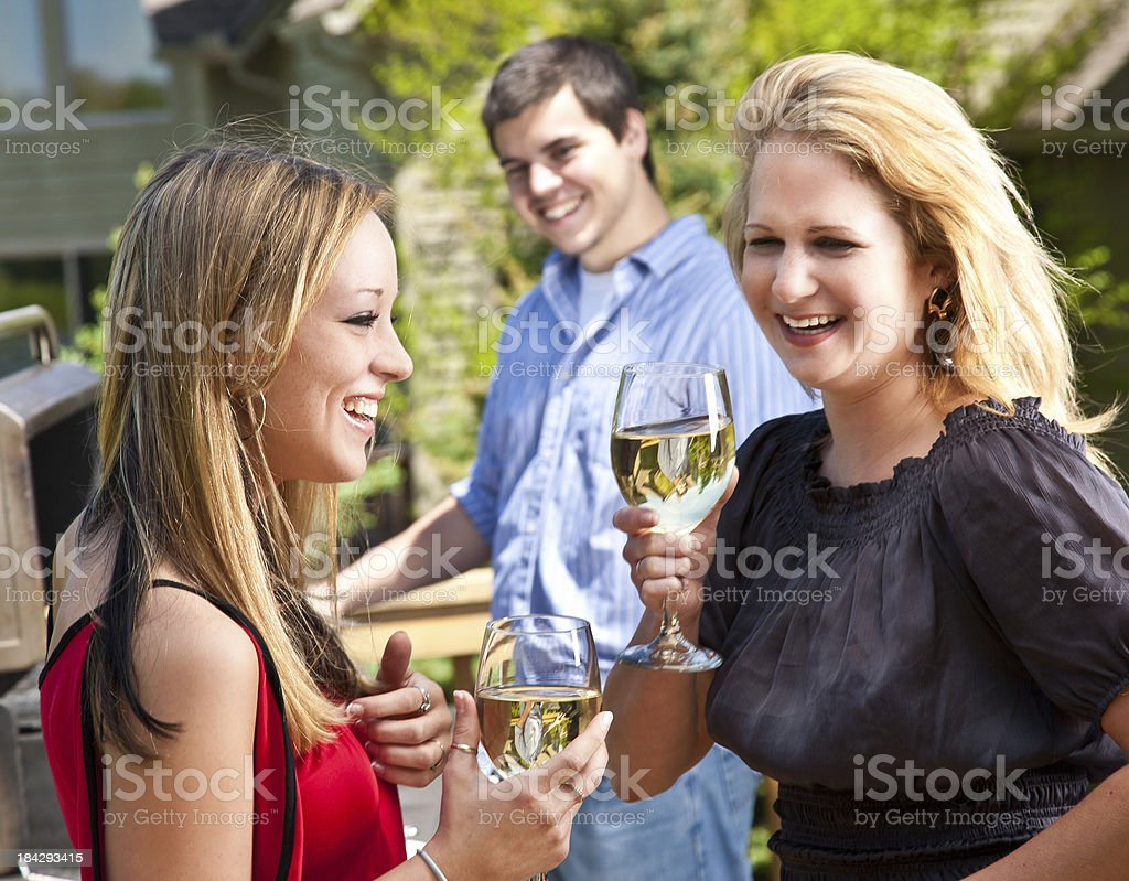 Friends Having Fun with Wine and Grill on House Patio royalty-free stock photo
