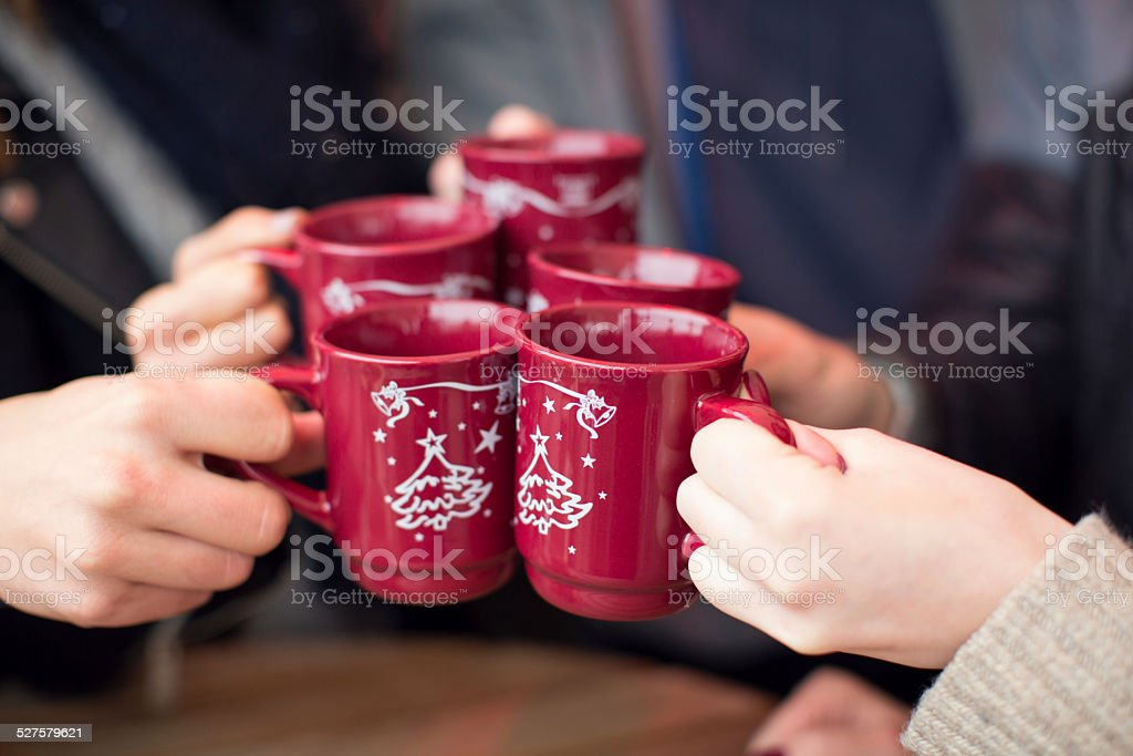 Friends having hot drinks outdoors in winter city. stock photo