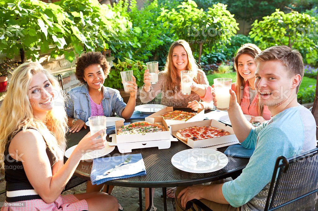 Friends Having Pizza Dinner in Outdoor Background Patio stock photo
