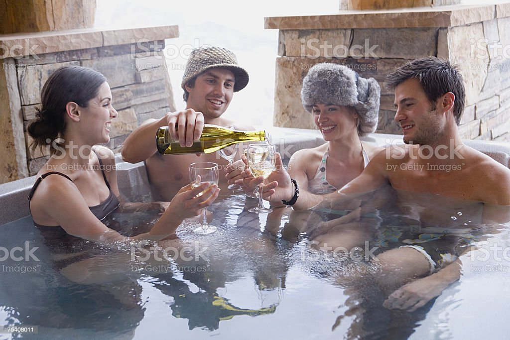Friends having wine in hot tub stock photo
