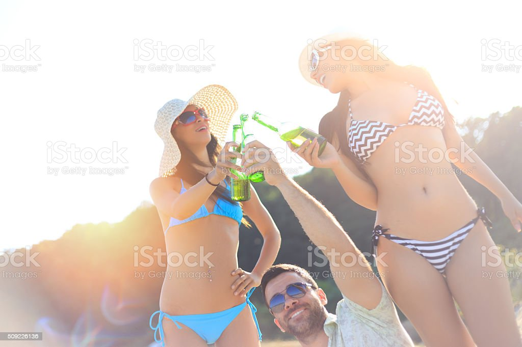 Friends holding beer bottle and celebrating on the beach stock photo