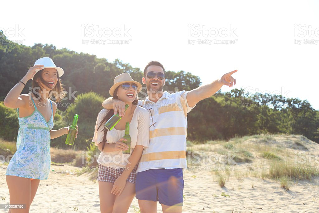 Friends holding beer bottle on beach,pointing at the sea stock photo