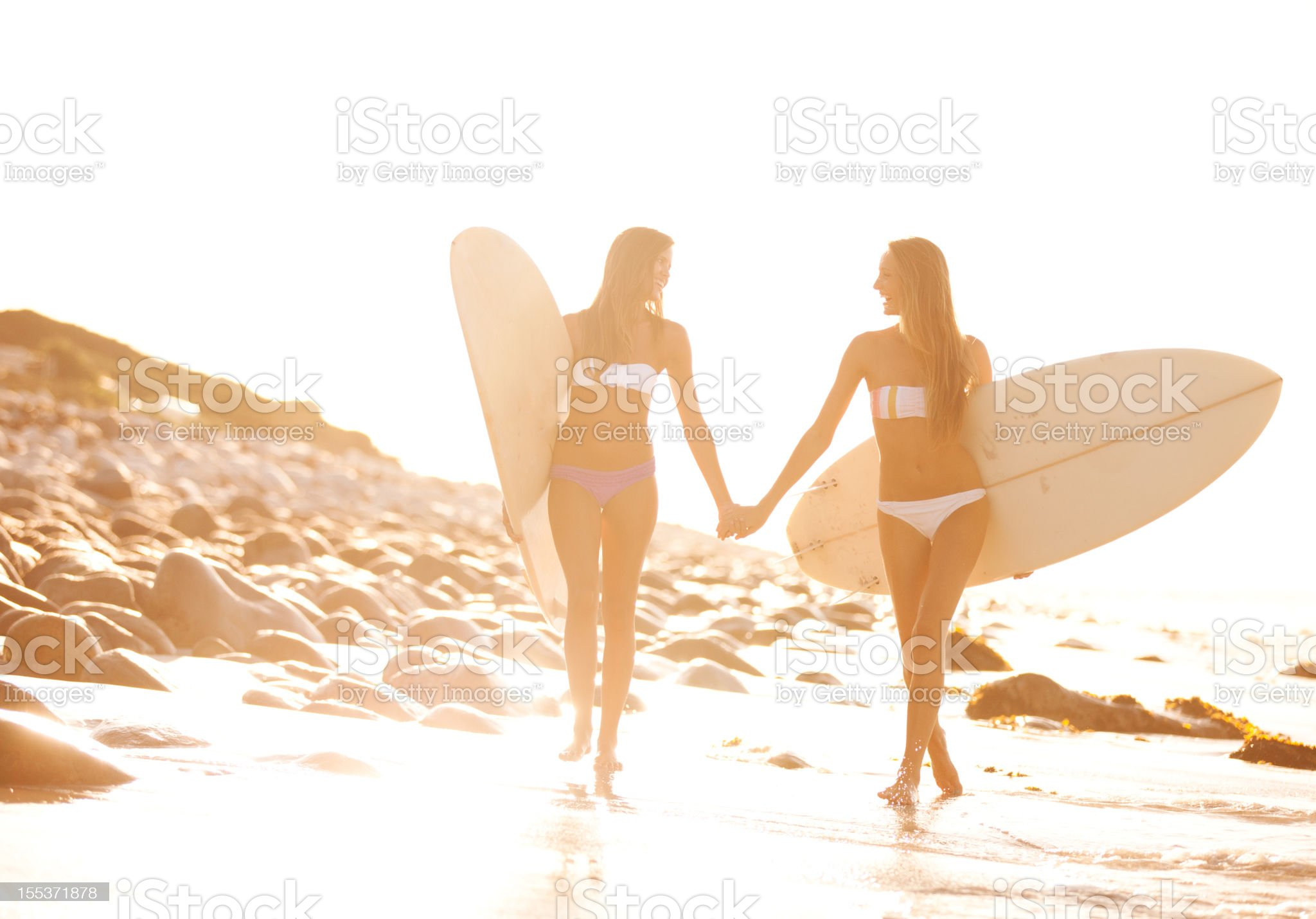 Friends holding hands as they return from a surf together royalty-free stock photo