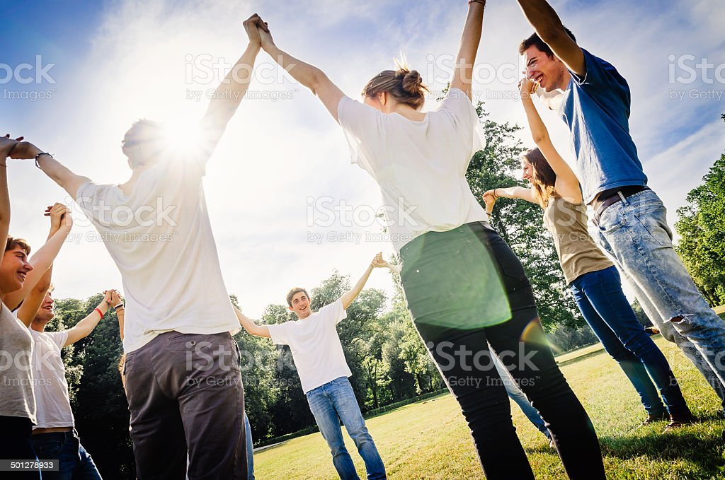Friends holding hands in the park stock photo