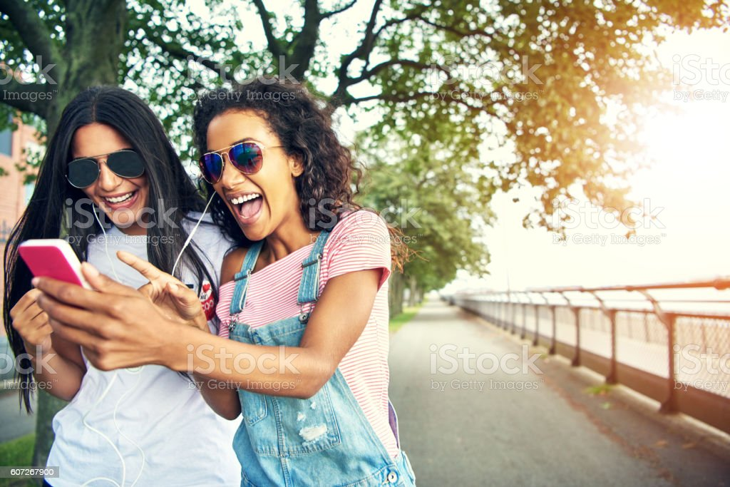 Friends holding mobile device pressing buttons stock photo