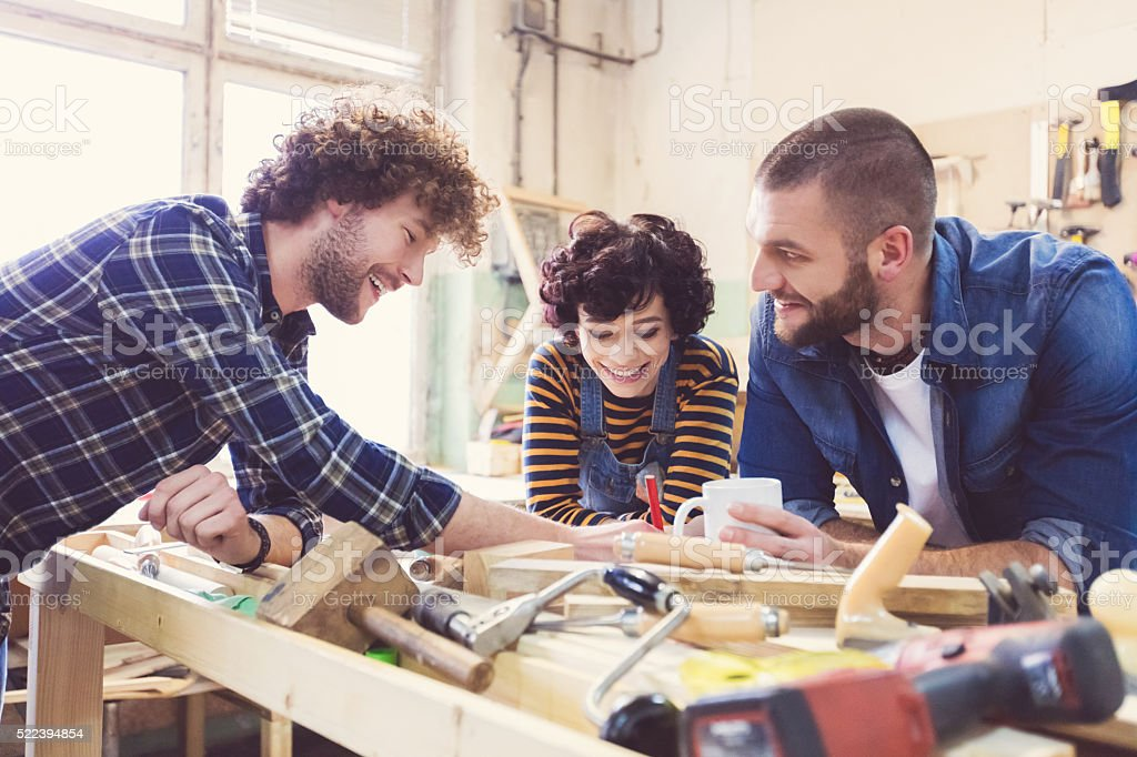 Friends in a construction workshop, learning carpentry stock photo