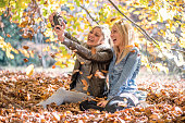 Friends in autumn outdoor park taking photo