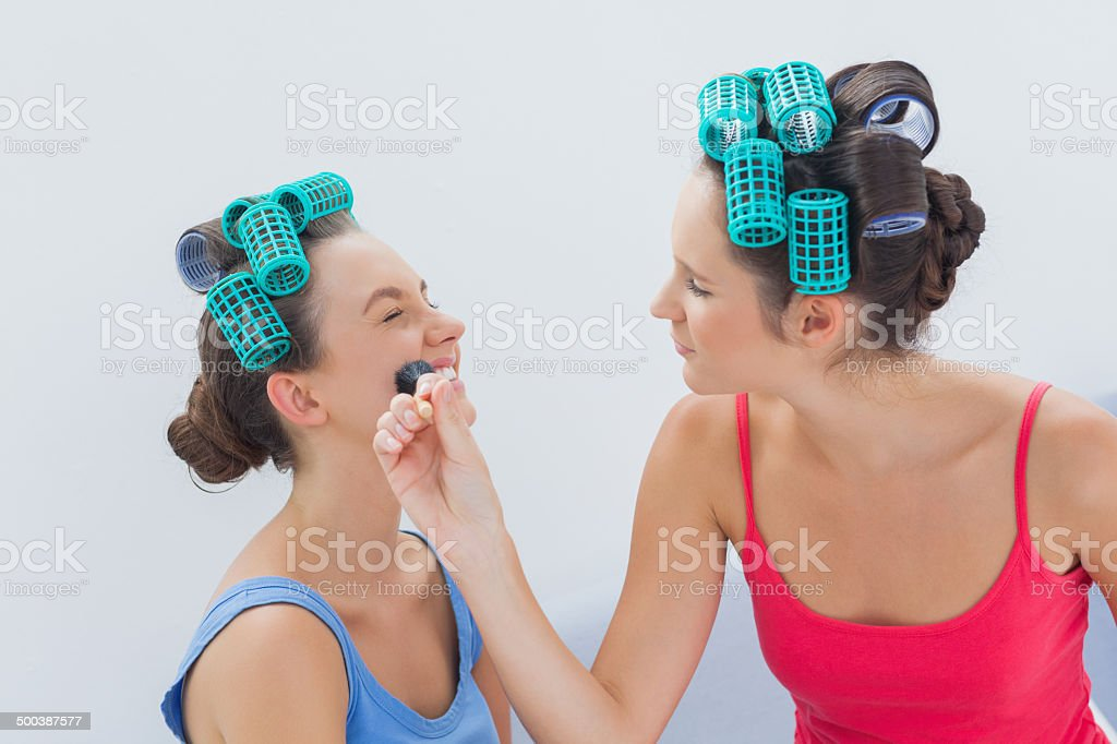 Friends in hair rollers having fun with makeup royalty-free stock photo