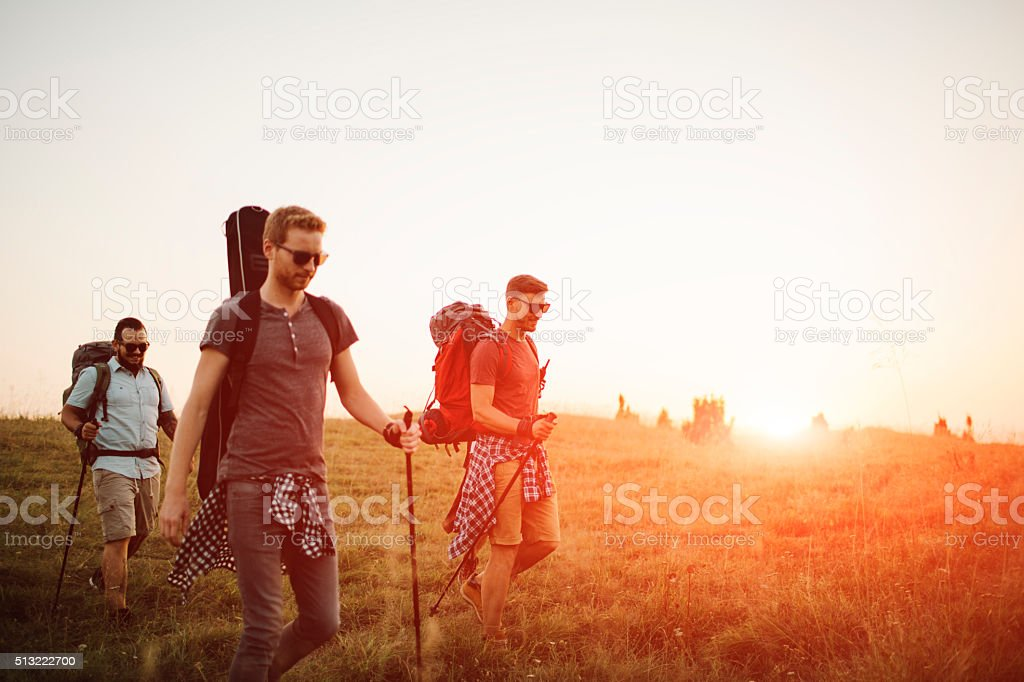 Friends In Hiking Adventure At Sunset. stock photo