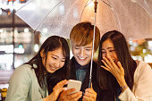 Friends in Japan under umbrella using cell phone