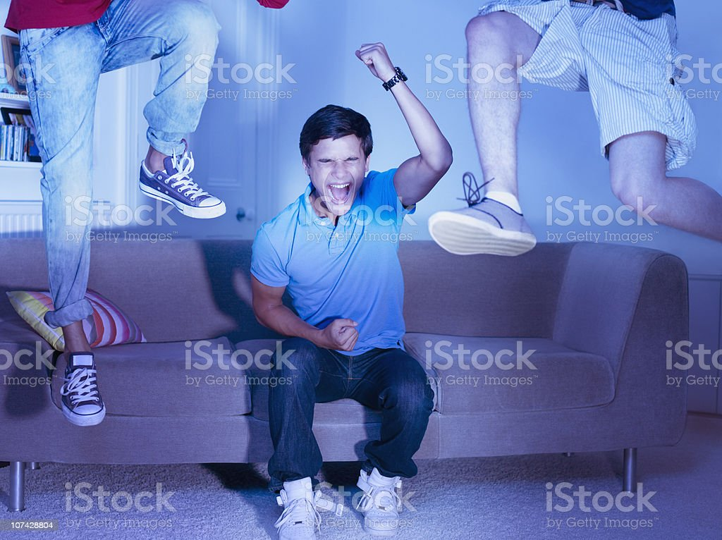 Friends in living room cheering and jumping stock photo