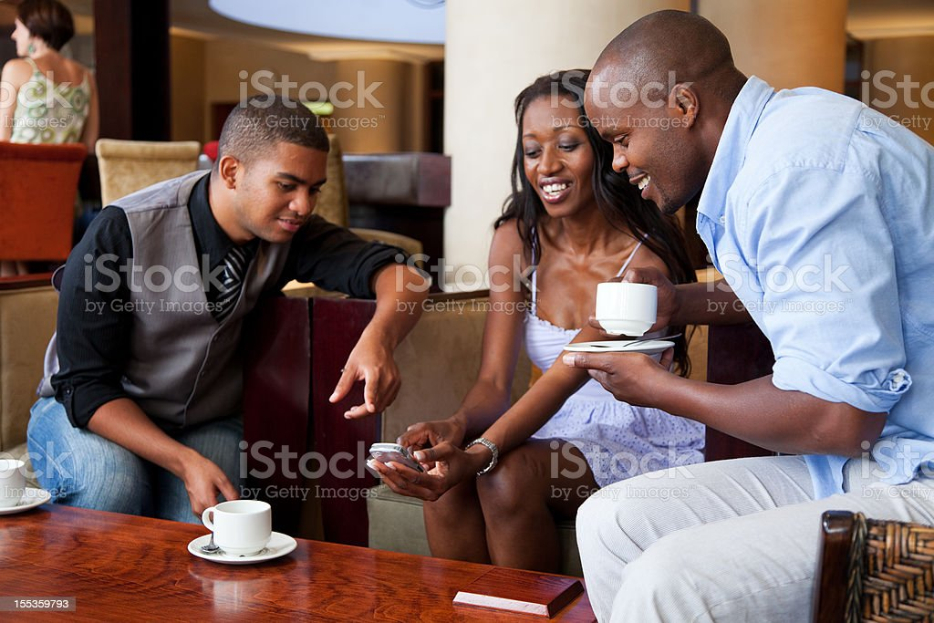 Friends In Lounge Having Coffee And Looking At Mobile Phone royalty-free stock photo