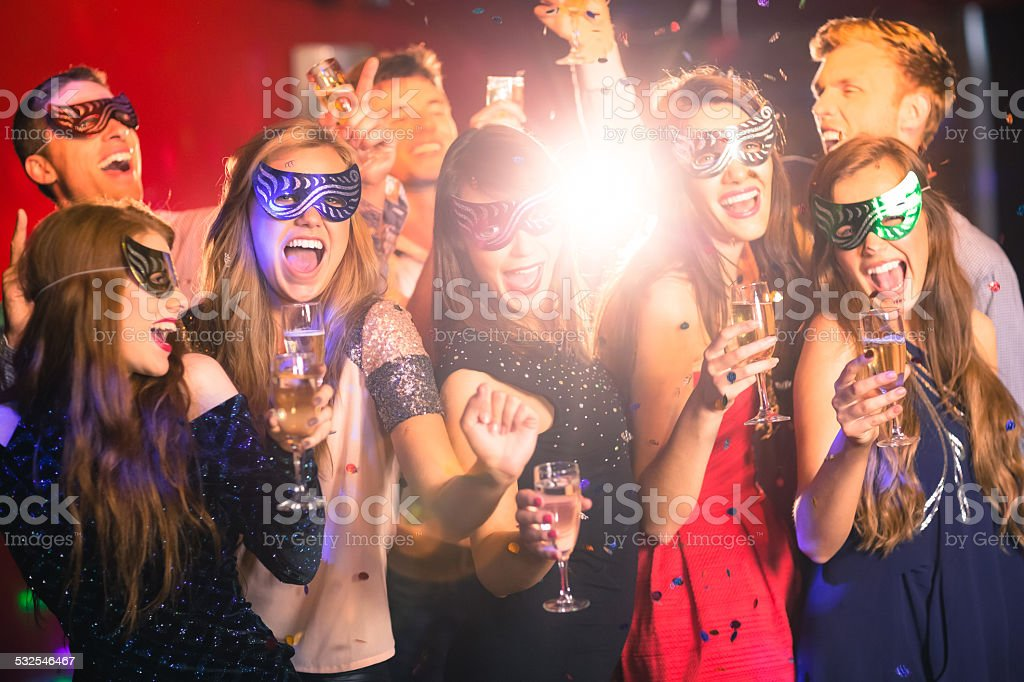 Friends in masquerade masks drinking champagne stock photo