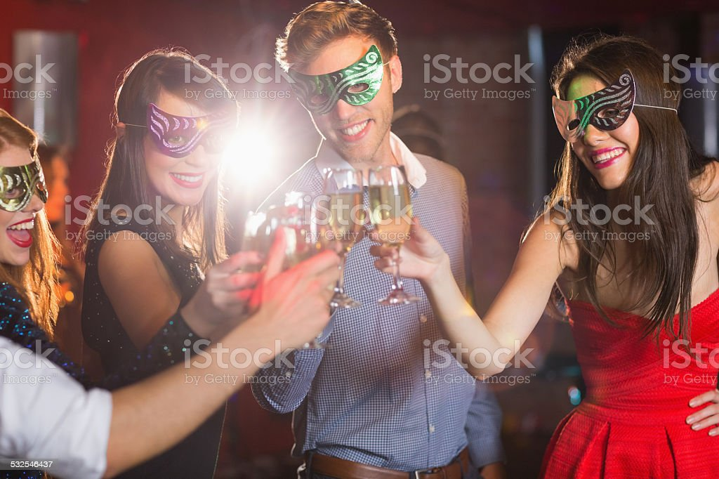 Friends in masquerade masks toasting with champagne stock photo