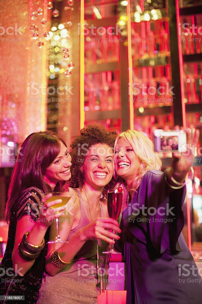 Friends in nightclub taking self-portrait with digital camera royalty-free stock photo
