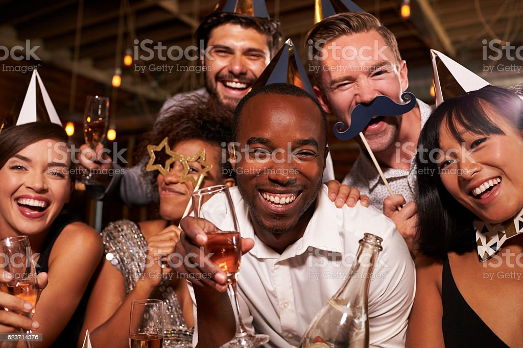 Friends in party hats celebrating New Year at bar, stock photo