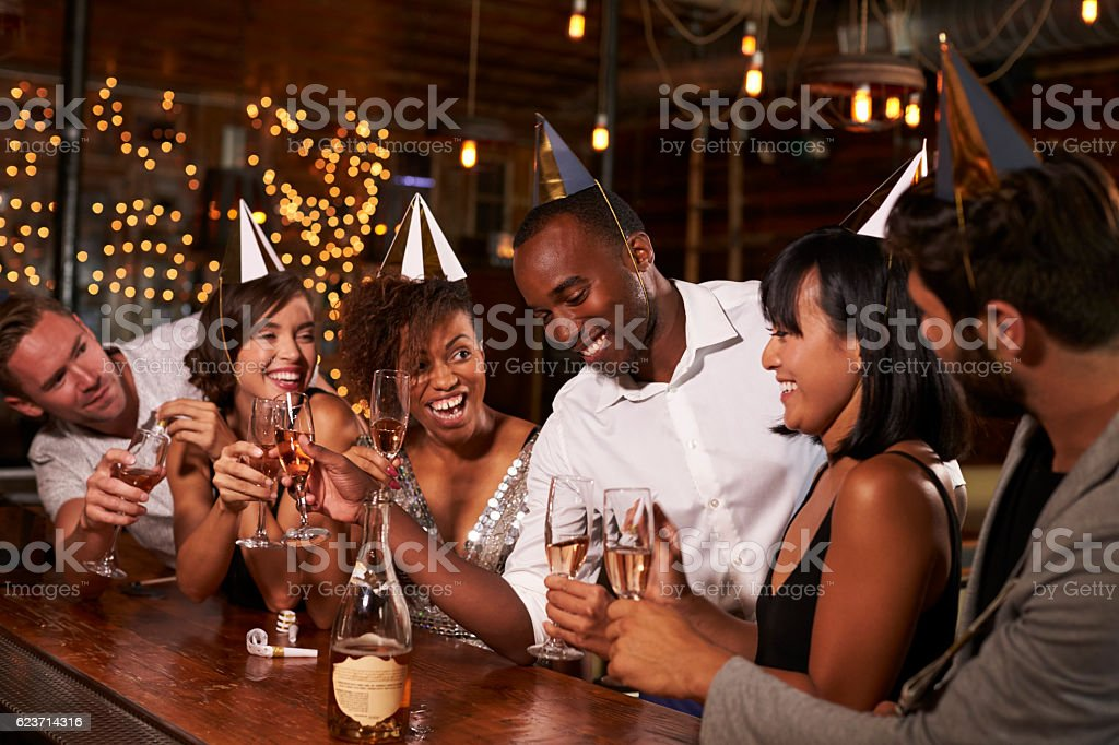 Friends in party hats celebrating New Year at party in a bar stock photo