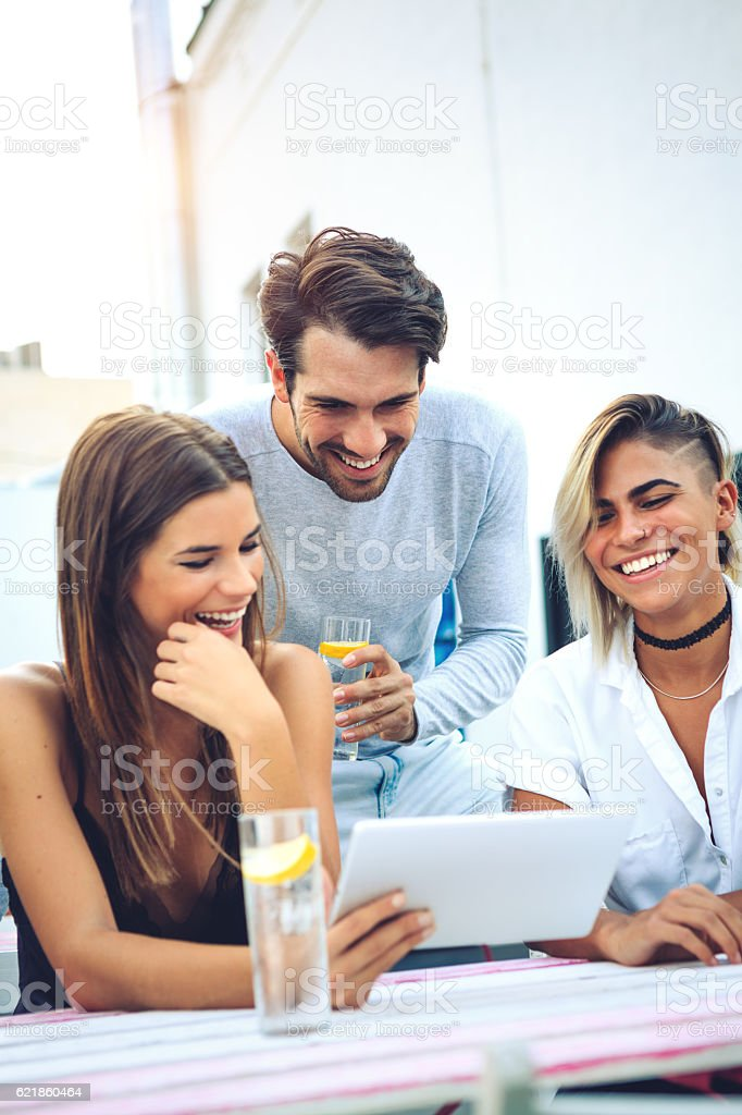 Friends In The Bar Looking At Photos On Digital Tablet stock photo