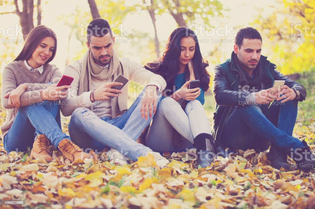 Friends in the park with smart phones stock photo