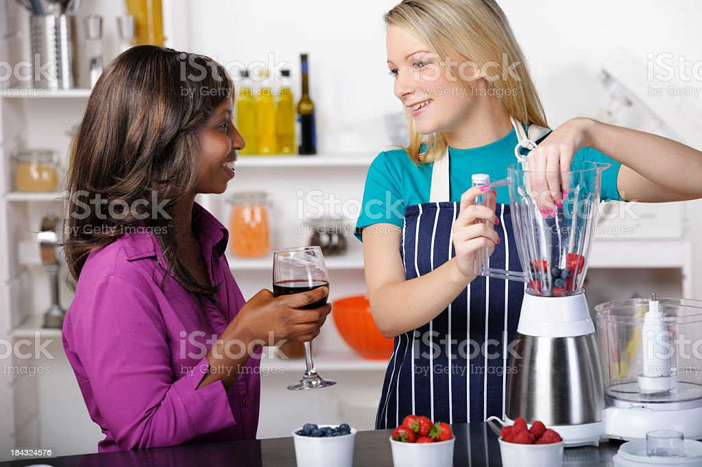 Friends Interacting While Preparing Healthy Drink/ Dessert royalty-free stock photo