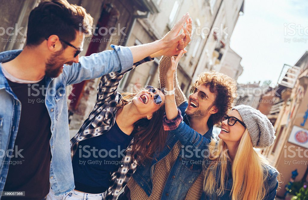 Friends joining hands outdoors stock photo