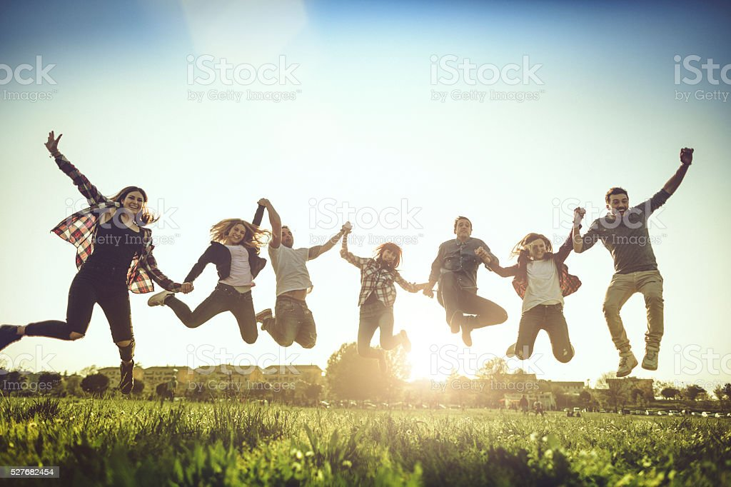 Friends jump together with raised arms stock photo