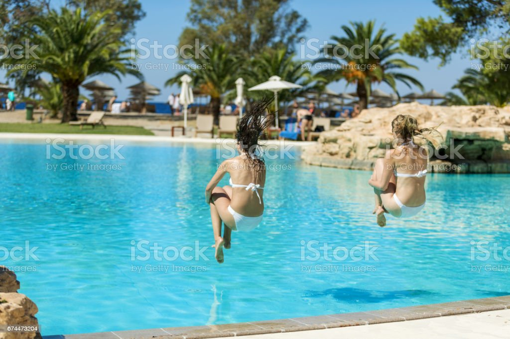 Friends jumping into pool stock photo