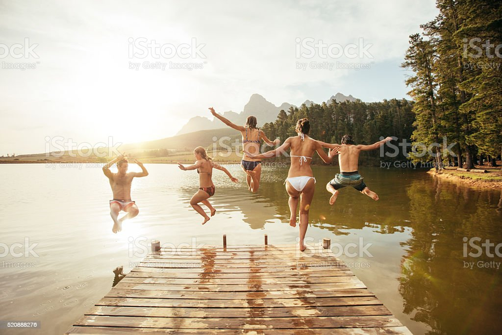 Friends jumping into the water from a jetty stock photo