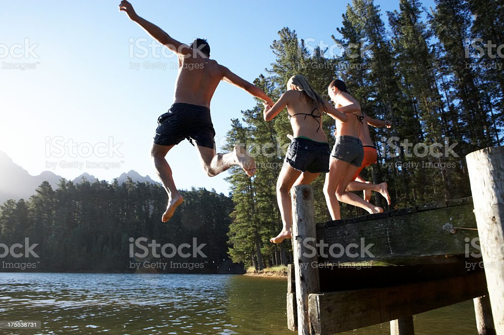 Friends jumping of of a dock into a lake royalty-free stock photo
