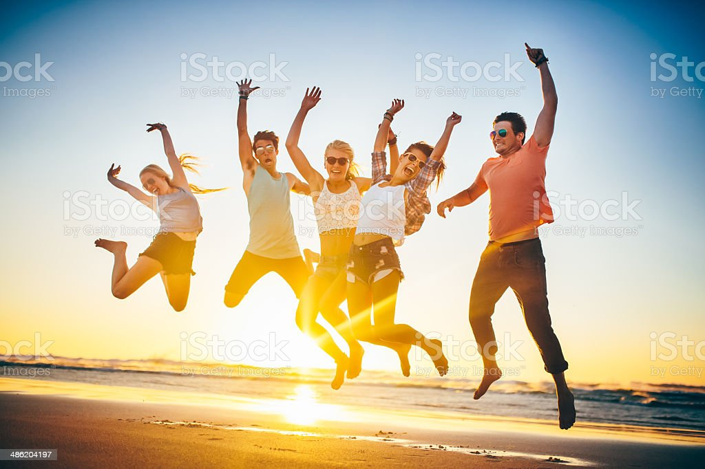 Friends jumping on beach in sunset royalty-free stock photo