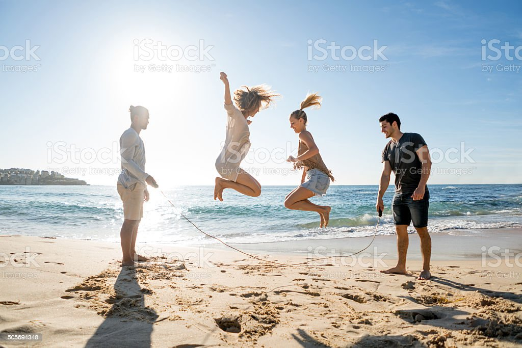 Friends jumping rope at the beach stock photo