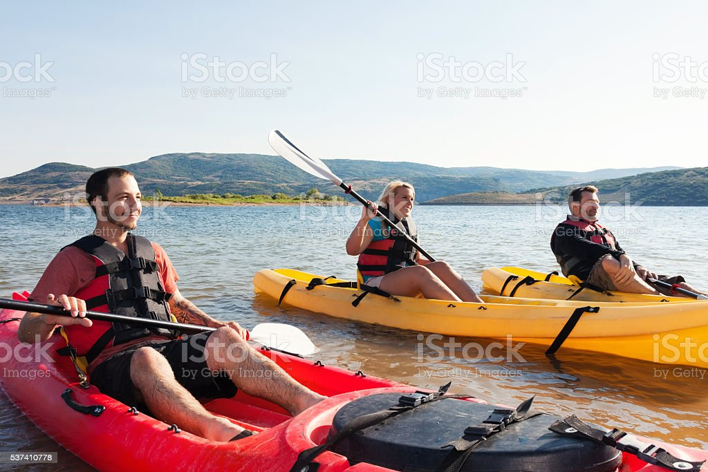 Friends kayak together on vacation stock photo