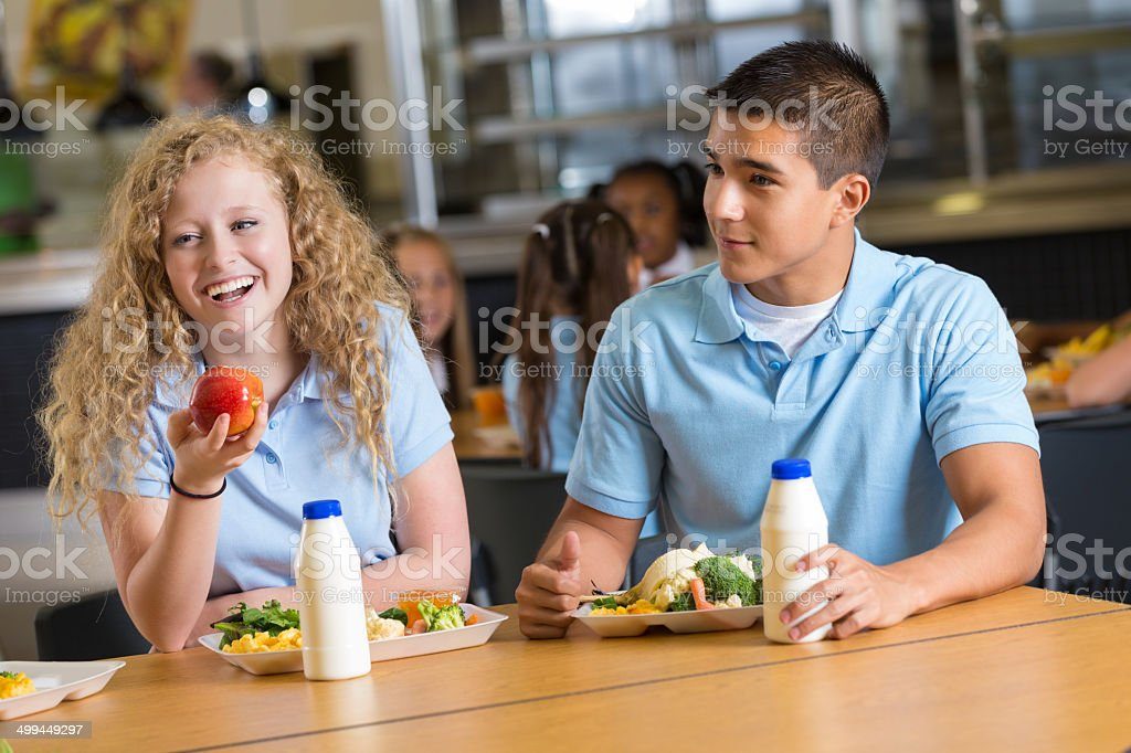 Friends laughing together while eating in school cafeteria stock photo