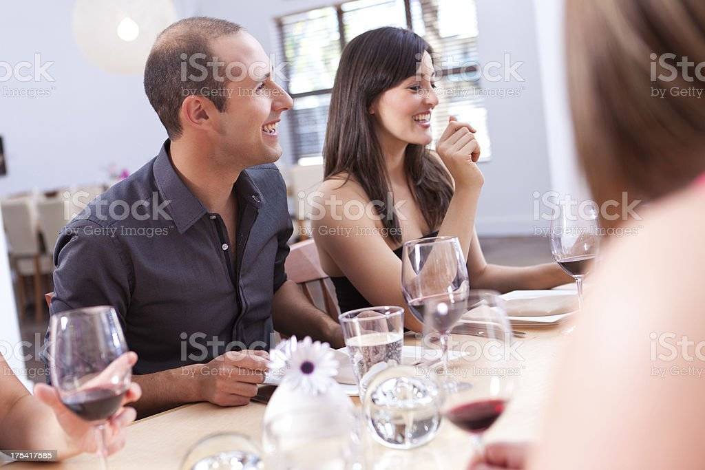 Friends laughing together while having dinner at a restaurant royalty-free stock photo