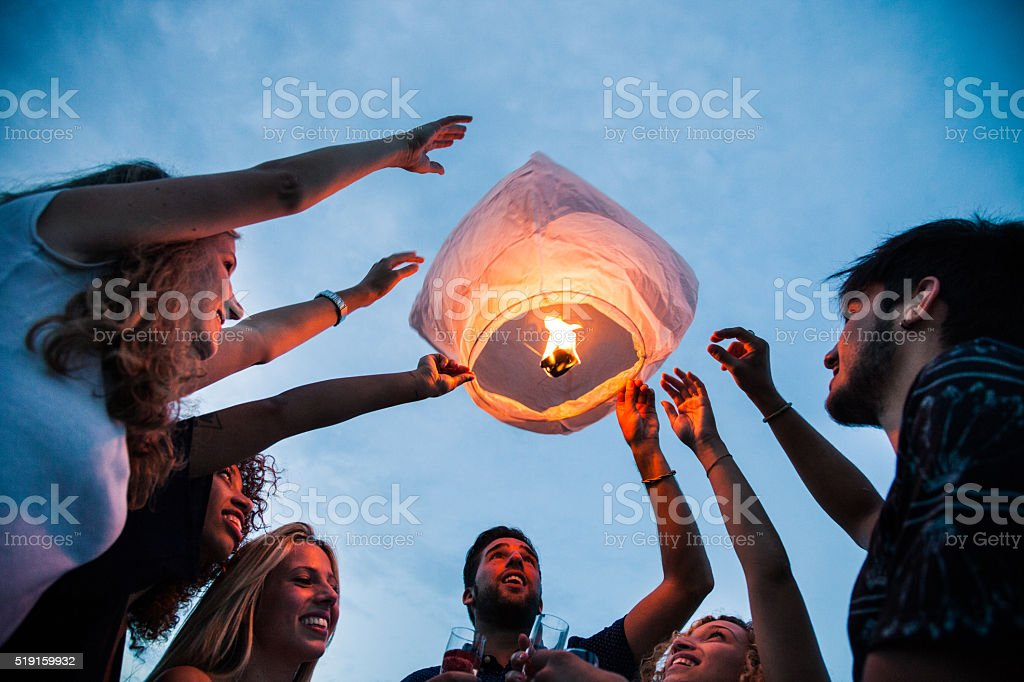 Friends lighting up a paper lantern at party stock photo